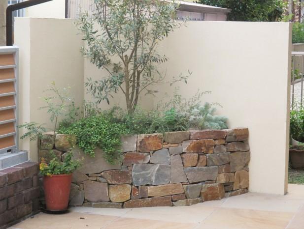 nissinn_n2庭の奥に石積みとオリーブの組み合わせ。衝立の奥に物置を隠して